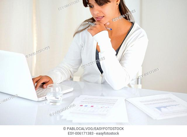 Portrait of a young woman working and reading on laptop screen at office indoor