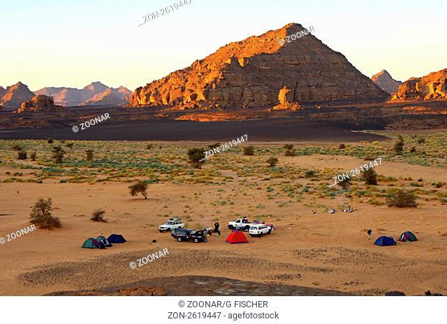 Blick von oben auf einen übernachtungsplatz mit Geländewagen und Zelten am Morgen im Akakus-Gebirge, Sahara, Libyen / Bird's eye morning view of a natural...