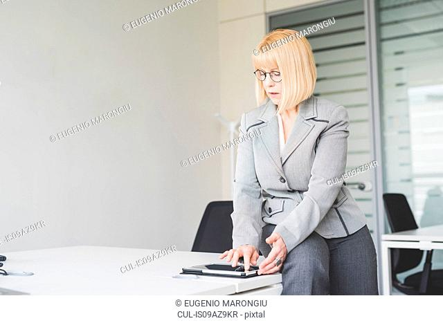 Mature businesswoman sitting on office desk using touchscreen on digital tablet