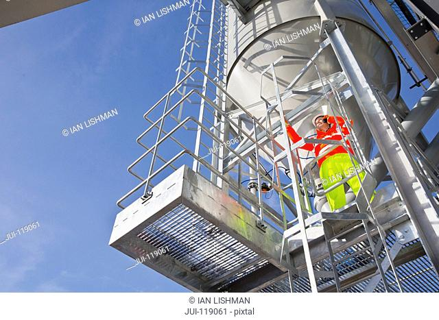 Engineer wearing hi viz using mobile phone on steel tower platform