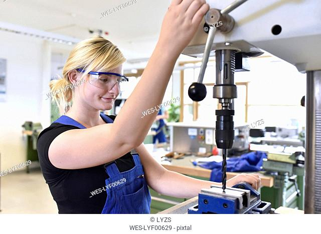 Female trainee working at press drill