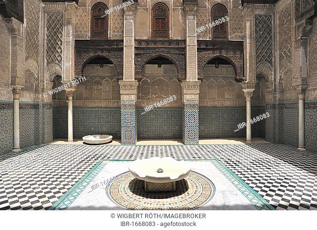 Partial view, courtyard with wash fountain in the Medersa Attarine, walls and arches with carved cedar wood, stucco ornaments and tile mosaics, Fes, Morocco