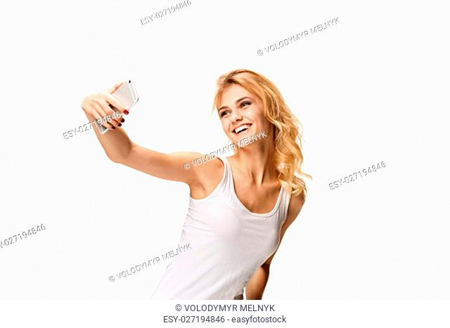 Portrait of beautiful smiling girl making selfie with modern cell phone in hands on white background