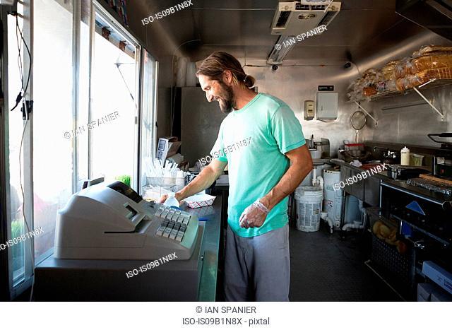 Man preparing food for customer in fast food trailer