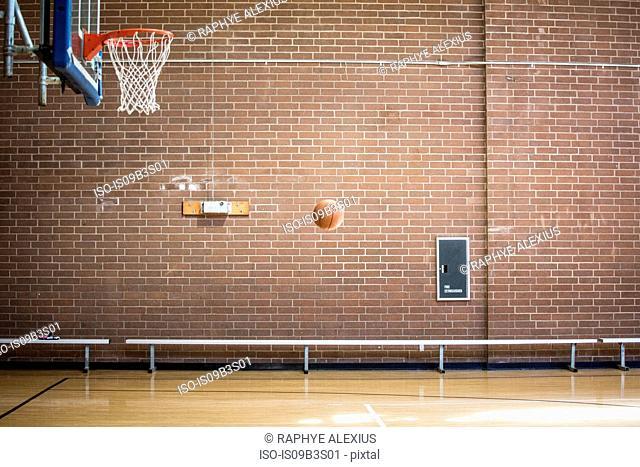 Basketball ball mid air on empty basketball court