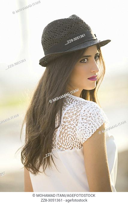 Beautiful young woman wearing a hat looking over shoulder