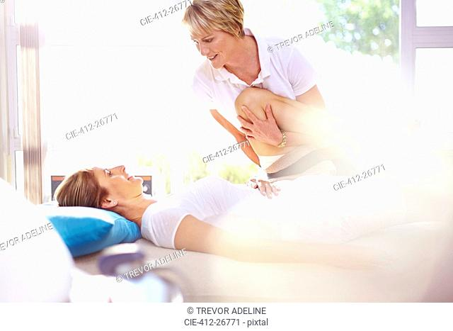 Physical therapist stretching woman's leg
