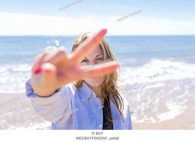 Portrait of young woman looking through her fingers showing victory sign