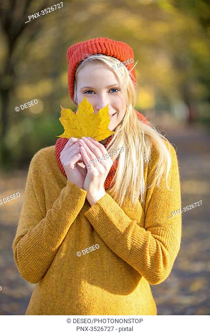 Portrait of a pretty blonde woman in park in autumn with leaf covering partially her face