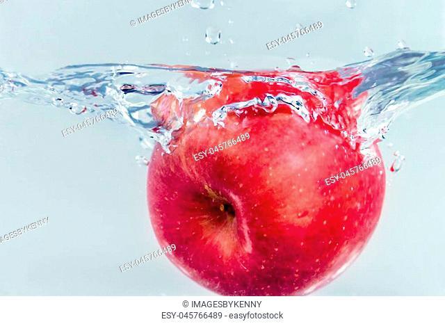 Apple falling into water splashing