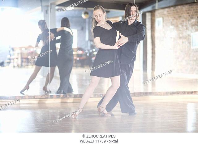 Couple dancing tango in studio