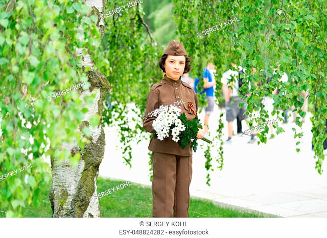 Portrait of a boy with flowers, in the uniform of a soldier of the Red Army during the Second World War