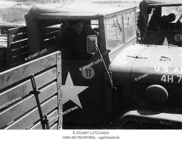 A photograph of two United States Army M35 military trucks with their drivers, the closest driver is posing for the image while the other is examining something...