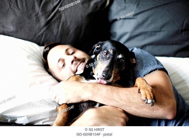Young man reclining on bed hugging dog