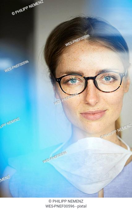 Portrait of woman with surgical mask wearing glasses