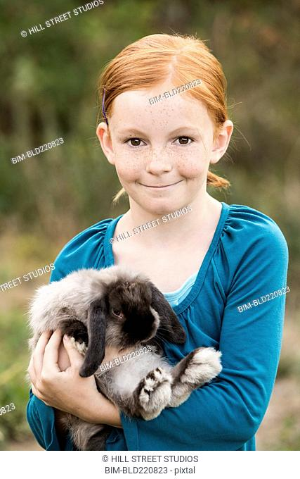 Girl carrying rabbit outdoors