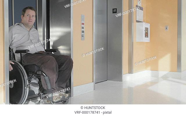 Man with spinal cord injury in wheelchair exiting an elevator