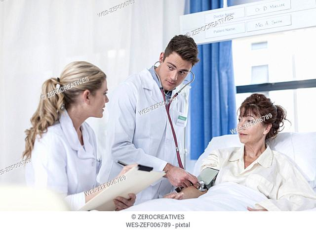 Doctor and nurse examining woman in hospital bed