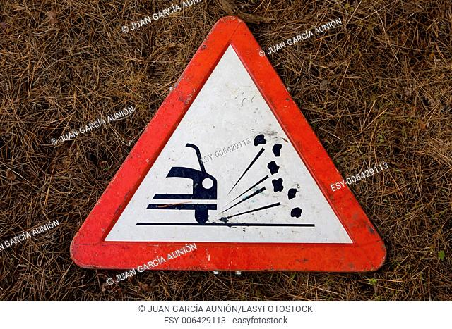 triangle traffic sign for gravel isolated over dry grassy background