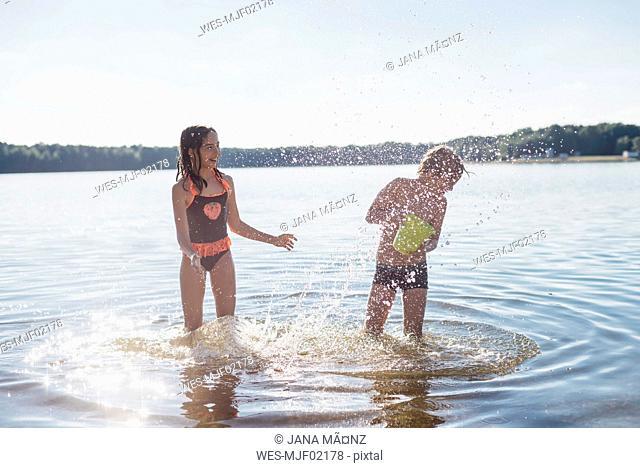 Boy and girl splashing with water at lakeshore