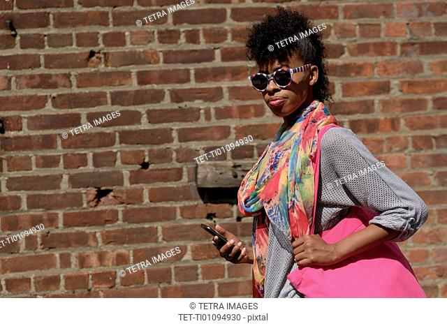 Young woman against brick wall