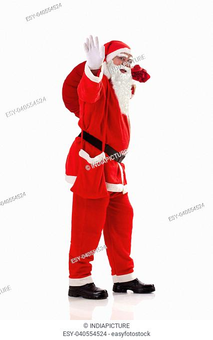 Full length of Santa Claus waving while carrying sack full of presents over white background