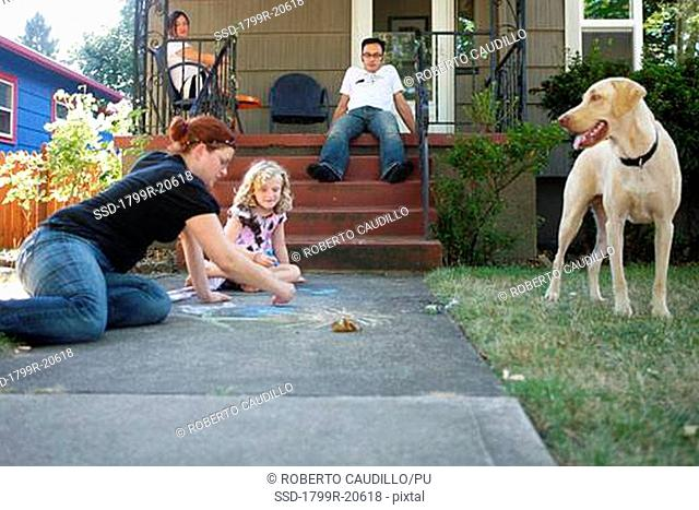 Girl playing with her mother in the front yard of a house