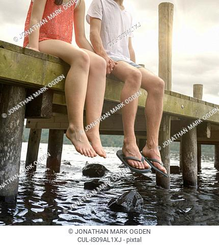 Young couple holding hands together and sitting on edge of jetty over lake
