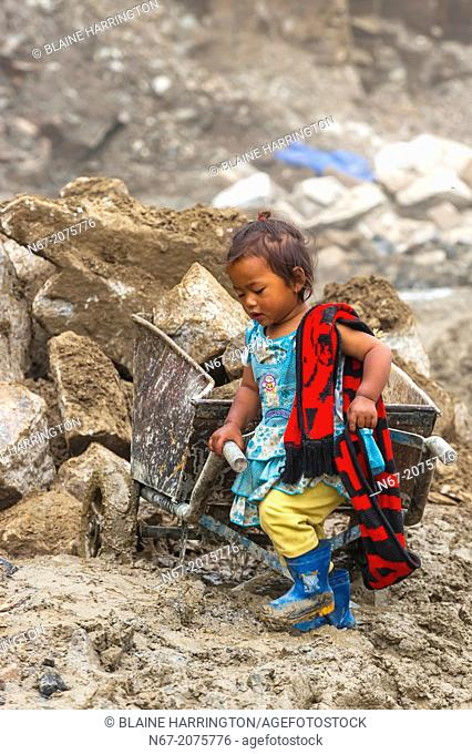 Little Nepalese girl stays with her mother as she works at a construction site on Rohtang Pass in Himachal Pradesh, India