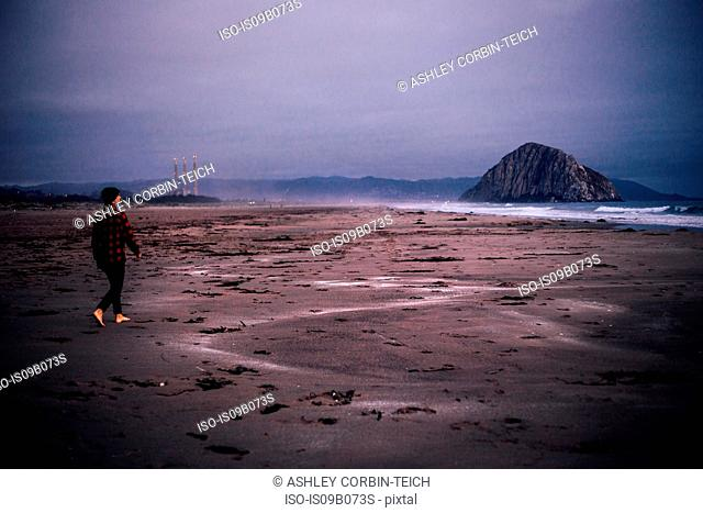 Man walking barefoot on overcast beach, Morro Bay, California, USA