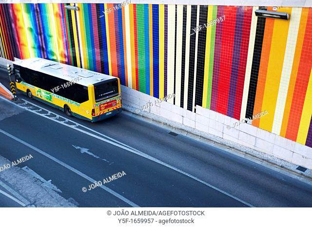 Bus passing by wall of color stripes