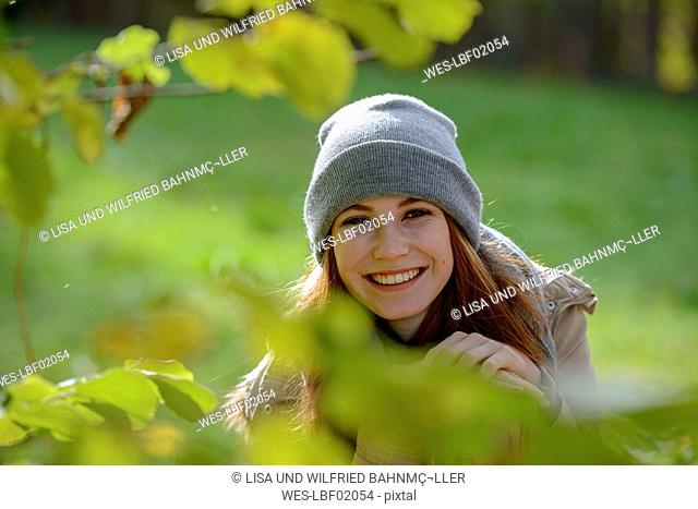 Portrait of smiling teenage girl in autumnal forest