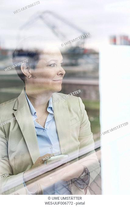 Businesswoman with cell phone behind windowpane