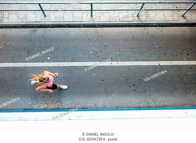 Overhead view of young female runner running along walkway