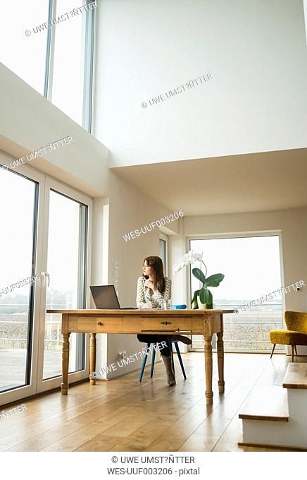 Young woman with laptop at wooden table looking out of window