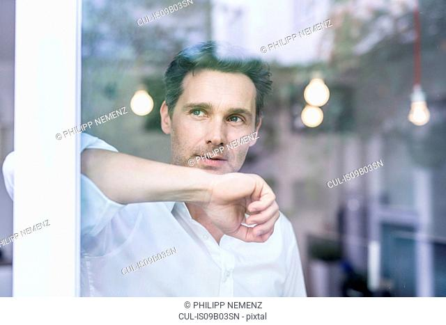 Businessman leaning against and looking through office window