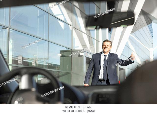 Businessman hailing a taxi outside airport building