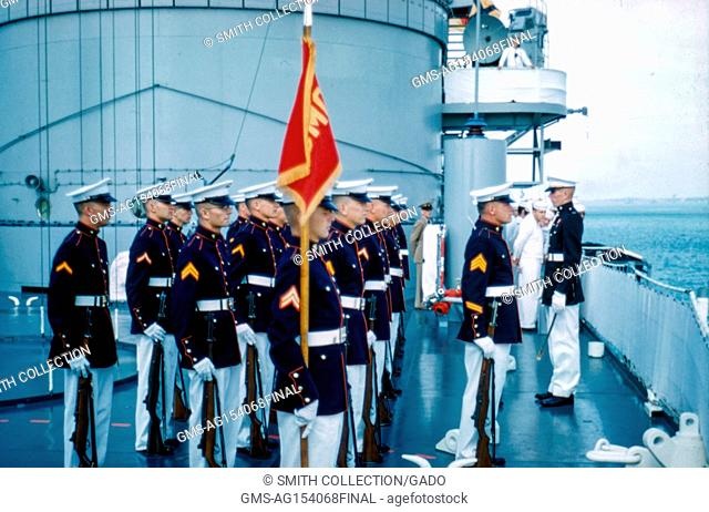 A group of United States Marine Corps (USMC) members in uniform stand at attention and present a flag on board a ship, with United States Navy sailors in the...