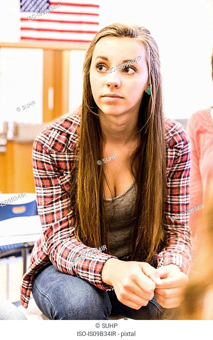 Teenage girl listening at desk in high school lesson