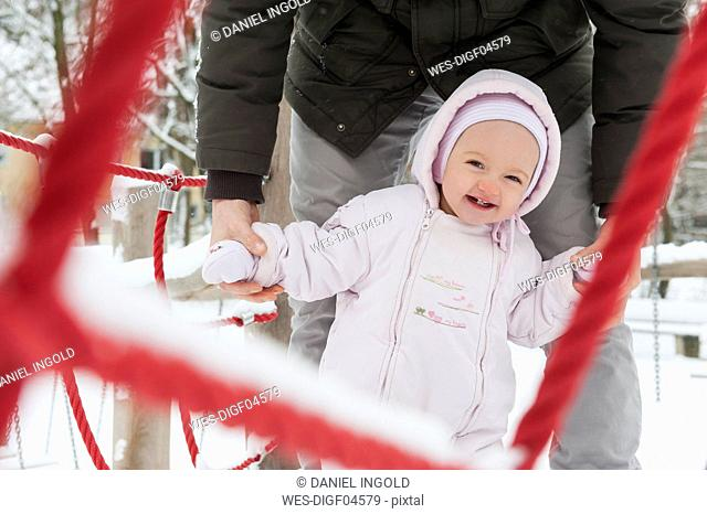 Portrait of smiling baby girl with father on playgroud in winter
