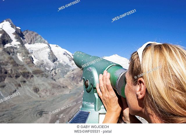 Austria, Carinthia, woman looking through binocular pointing at Grossglockner peak and Pasterze glacier, view from Kaiser-Franz-Josefs-Hoehe