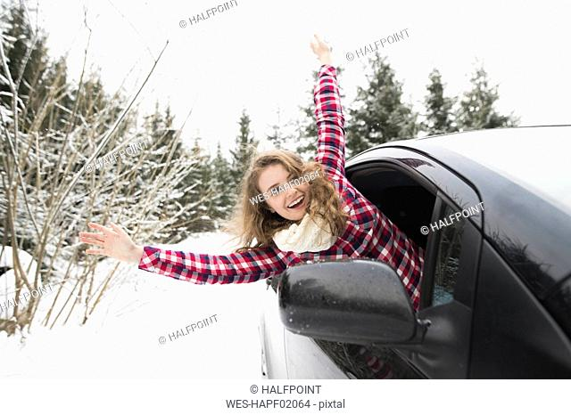 Portrait of laughing young woman leaning out of car window