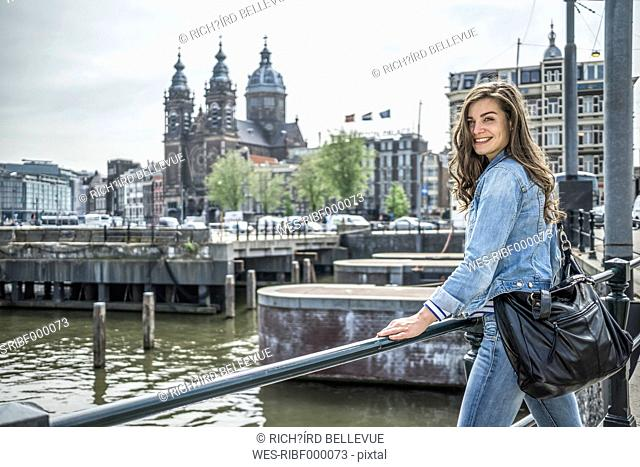 Netherlands, Amsterdam, female tourist in front of Amstel River