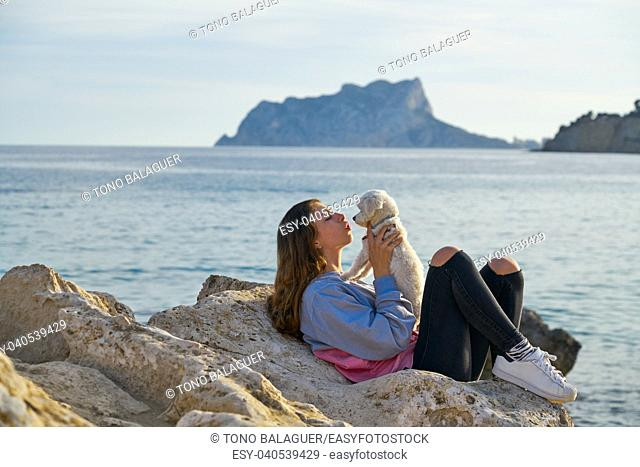 Girl playing with maltichon puppy dog in the beach