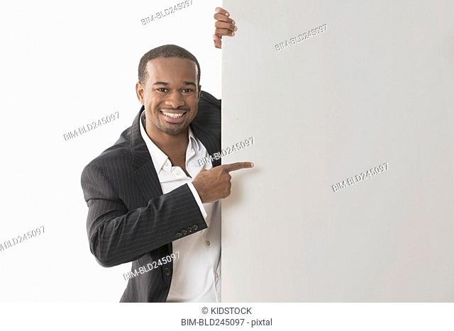 Smiling African American businessman pointing at blank placard