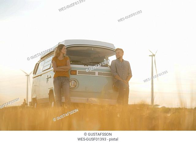 Happy couple at camper van in rural landscape with wind turbines in background