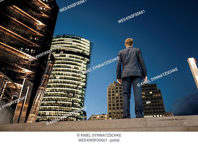 Germany, Berlin, Potsdamer Platz, back view of businessman at night