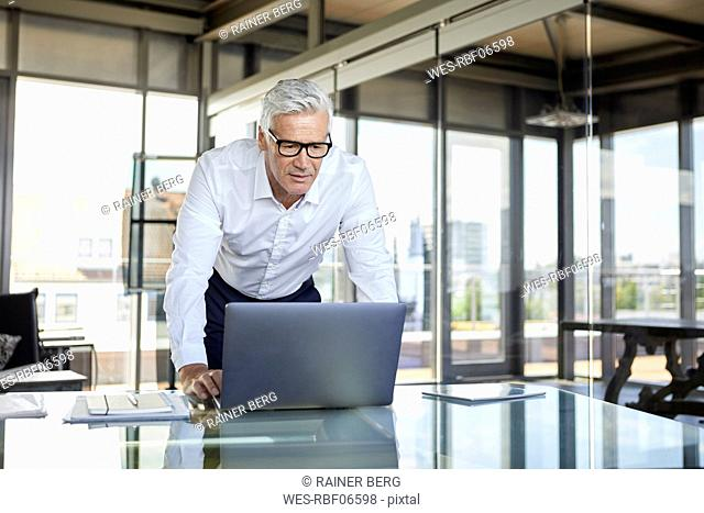 Businessman standing at desk, looking at laptop
