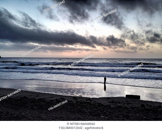Lone fisherman at dusk on a beach in Pacifica, California, USA