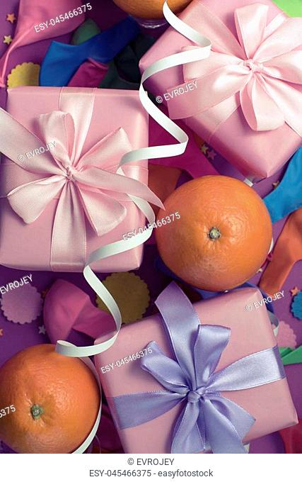 Decorative composition Three boxes with gifts Satin ribbon Bow Oranges Confetti Serpentine birthday party. The view from the top Vertical Toning